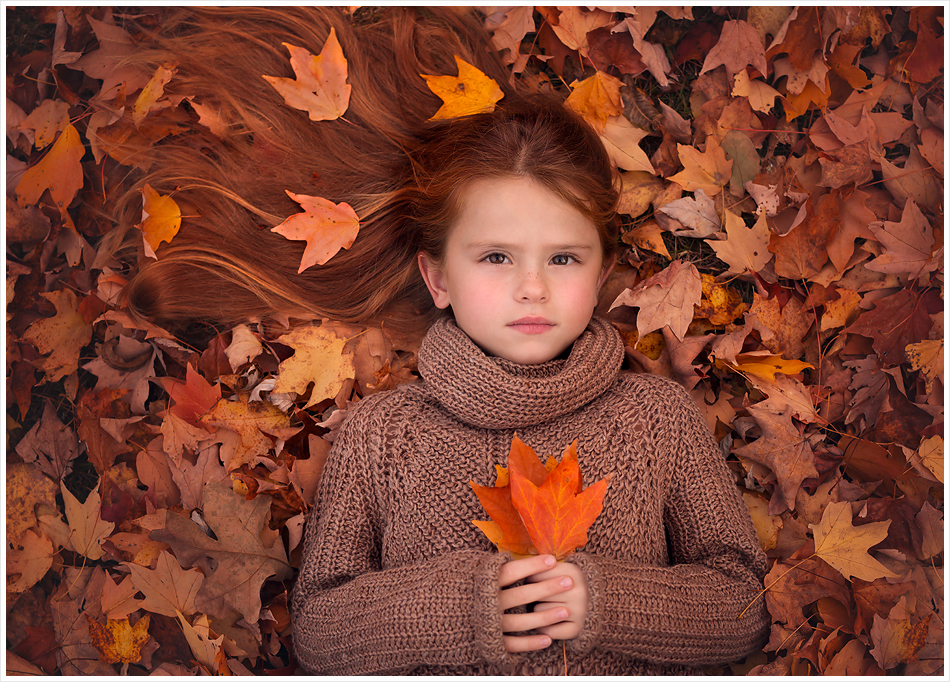 Little girl with long red hair lays in orange autumn leaves. LJHolloway Photography is a Las Vegas Child Photographer