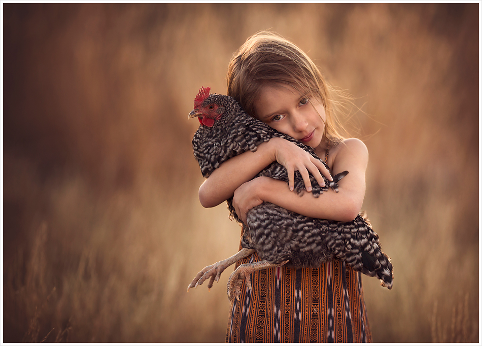 Little girl holds her pet chicken. LJHolloway Photography is a Las Vegas Child Photographer.