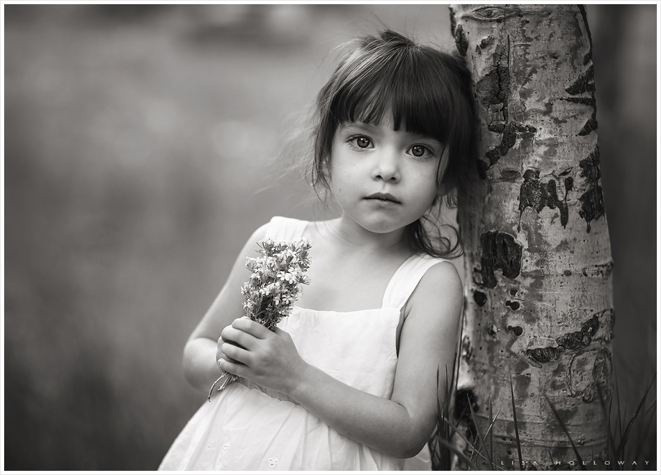 Black and white portrait of a little girl outdoors standing next to an aspen tree on