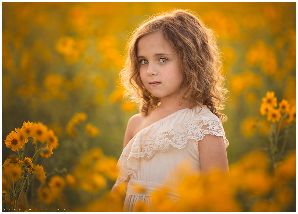 Little girl stands in a field of yellow wildflowers. LJHolloway Photography is a Las Vegas Child Photographer.