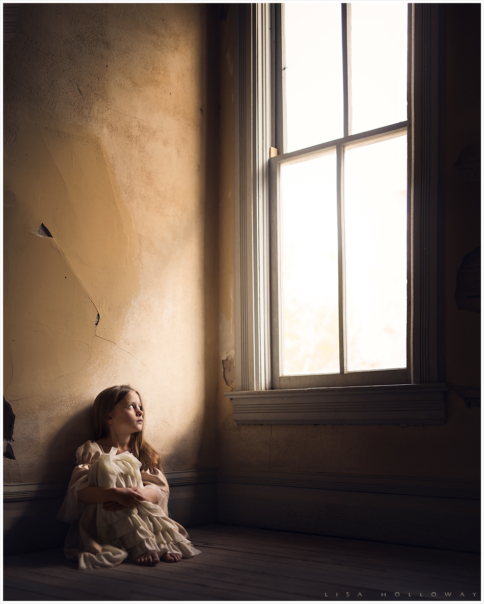 Little girl in period clothing sits inside a creepy, abandoned building looking wistfully out of the window. LJHolloway Photography is a Las Vegas Child Photographer.