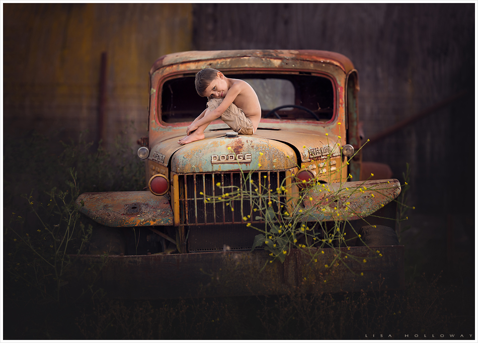 Little boy sits on a rusty vintage Dodge truck. LJHolloway photography is a Las Vegas Child Photographer.