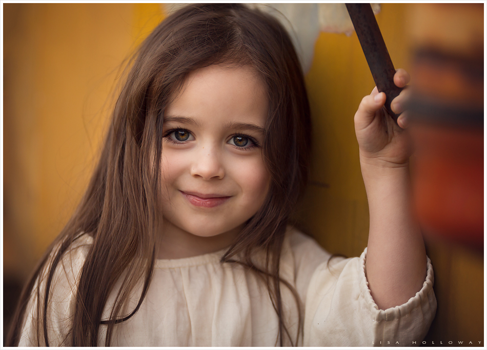 Cute little girl stands next to a yellow truck. LJHolloway photography is a Las Vegas Child Photographer.
