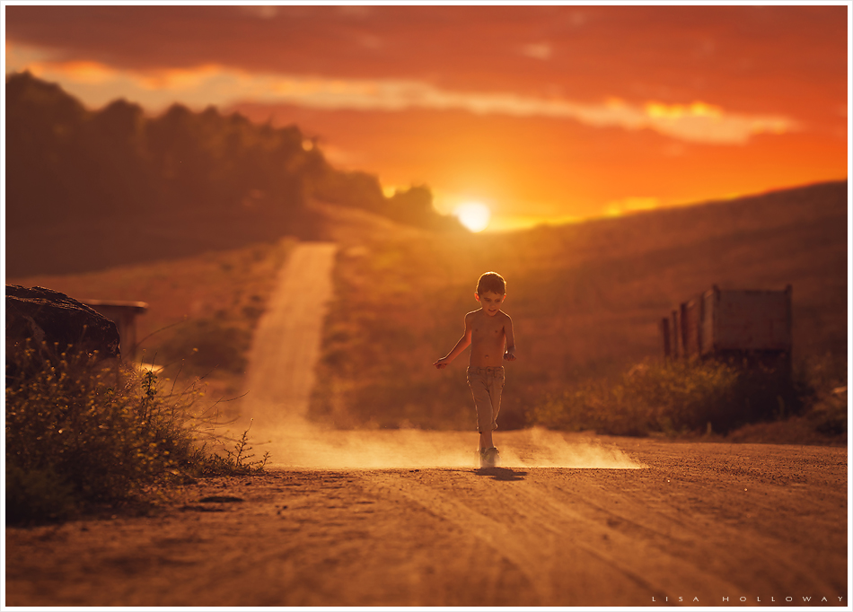Boy runs down a dusty road on a farm at sunset. LJHolloway photography is a Las Vegas Child Photographer.