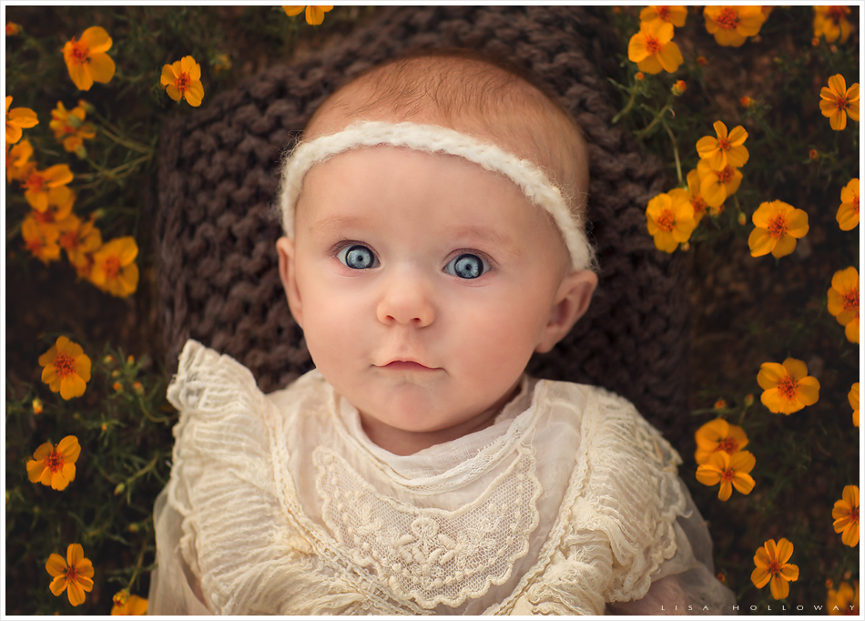 Closeup portrait of baby girl with blue eyes surrounded by yellow flowers. LJHolloway photography is a Las Vegas Child Photographer.