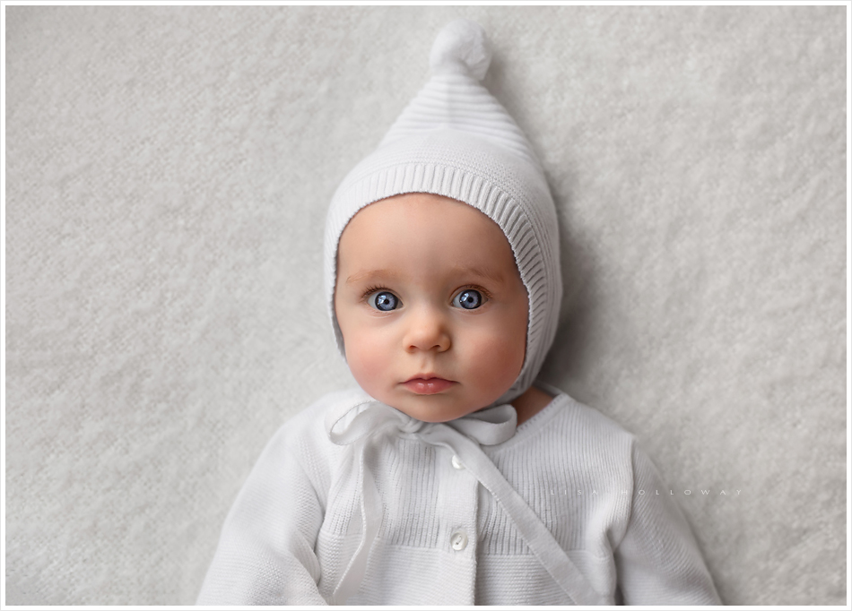 Beautiful baby girl with blue eyes wearing a white sweater and hat. LJHolloway photography is a Las Vegas Child Photographer.