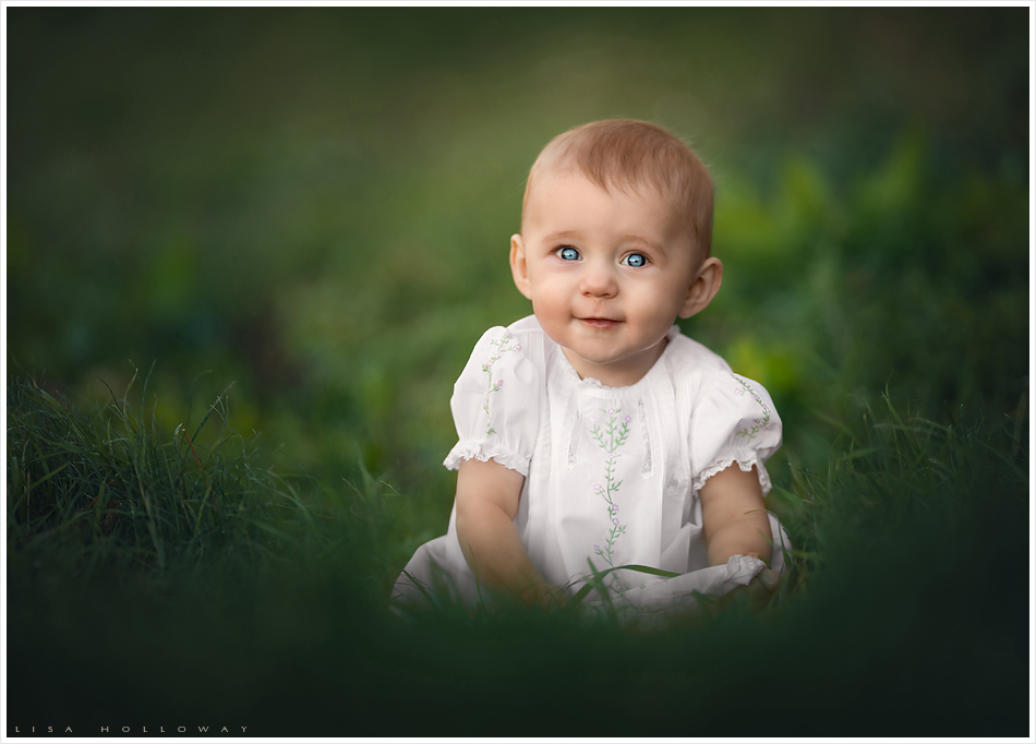 Portrait of a beautiful baby girl with blue eyes sitting in green grass ljholloway photography