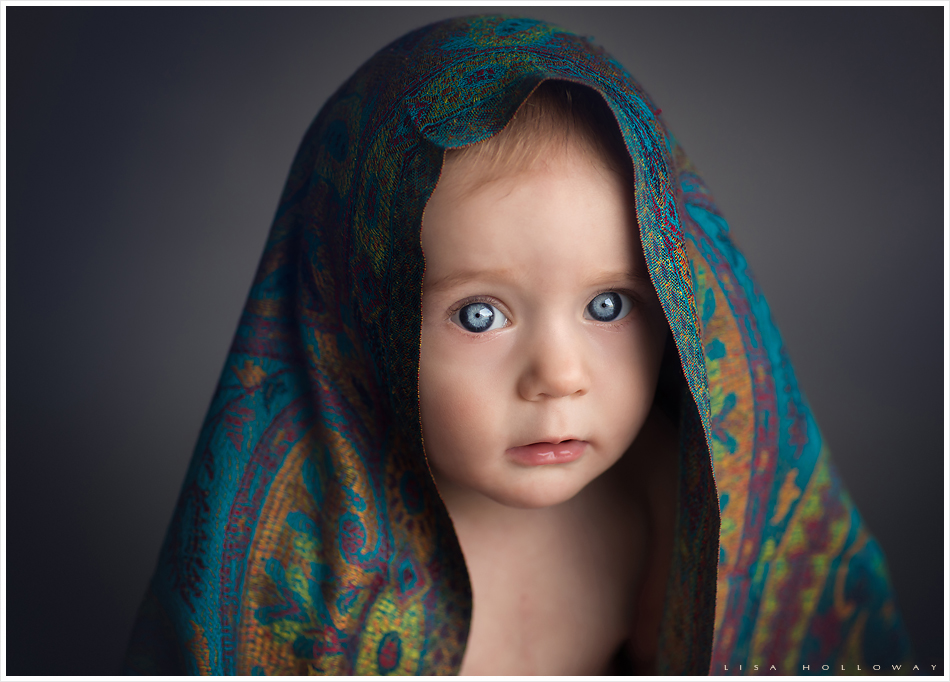 Beautiful close up portrait of a baby girl with blue eyes and a blue silk scarf over her head. LJHolloway Photography is a Las Vegas Baby Photographer.