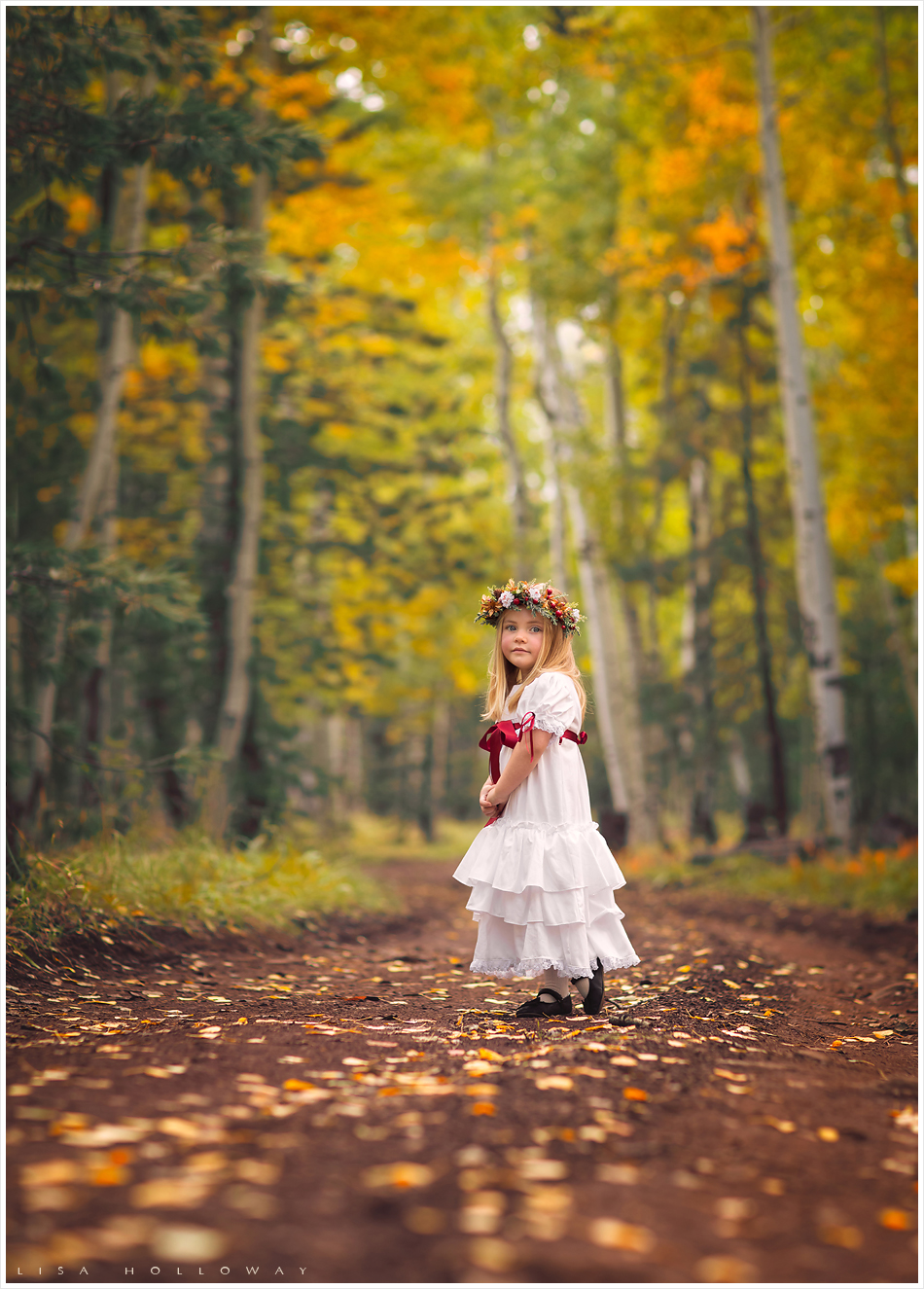 Adorable little blonde girl models a red and white Christmas dress in the fall aspen trees. LJHolloway Photography is a Las Vegas Child Photographer.