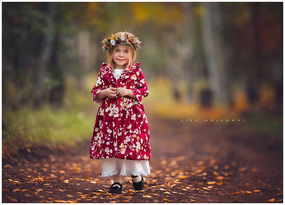 Adorable little blonde girl models a red and white christmas dress in the fall aspen trees