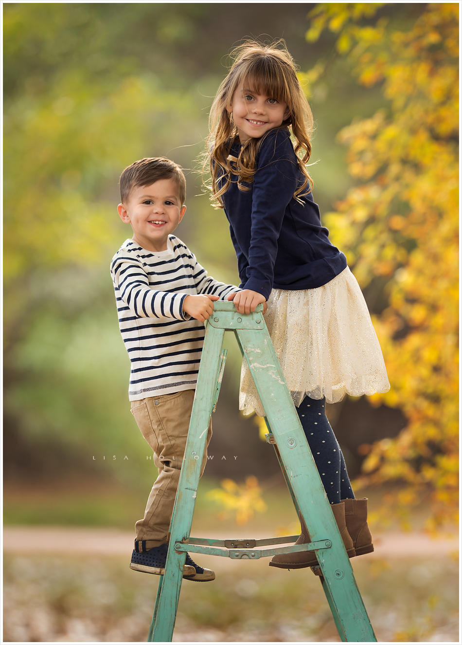 Adorable brother and sister pose on a blue wooden ladder for an outdoor portrait. LJHolloway Photography is a Las Vegas Family Photographer.