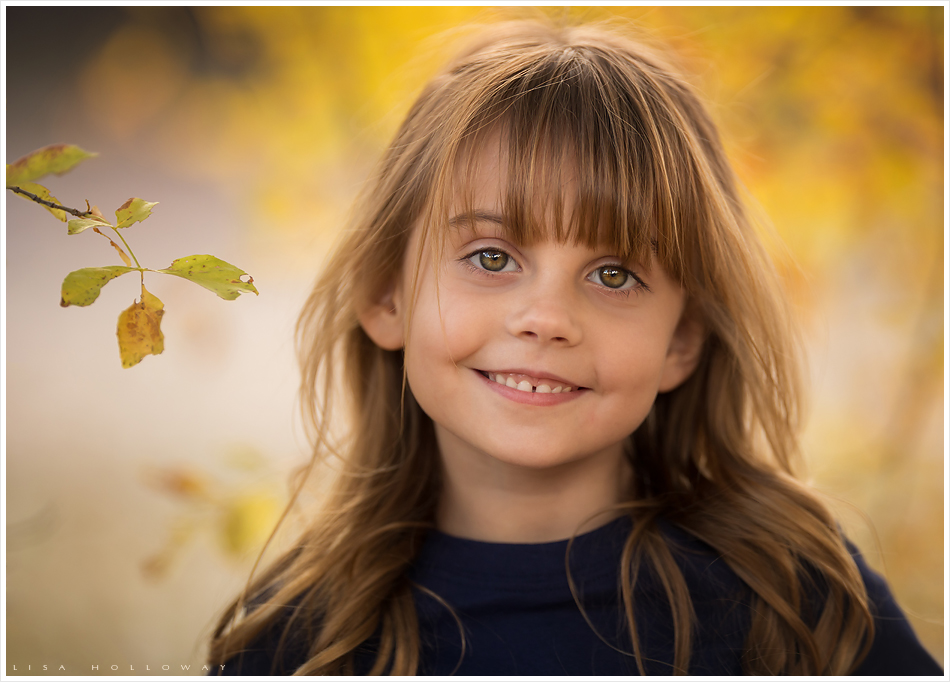Adorable little girl has an outdoor portrait taken in the fall colors. LJHolloway Photography is a Las Vegas Family Photographer.