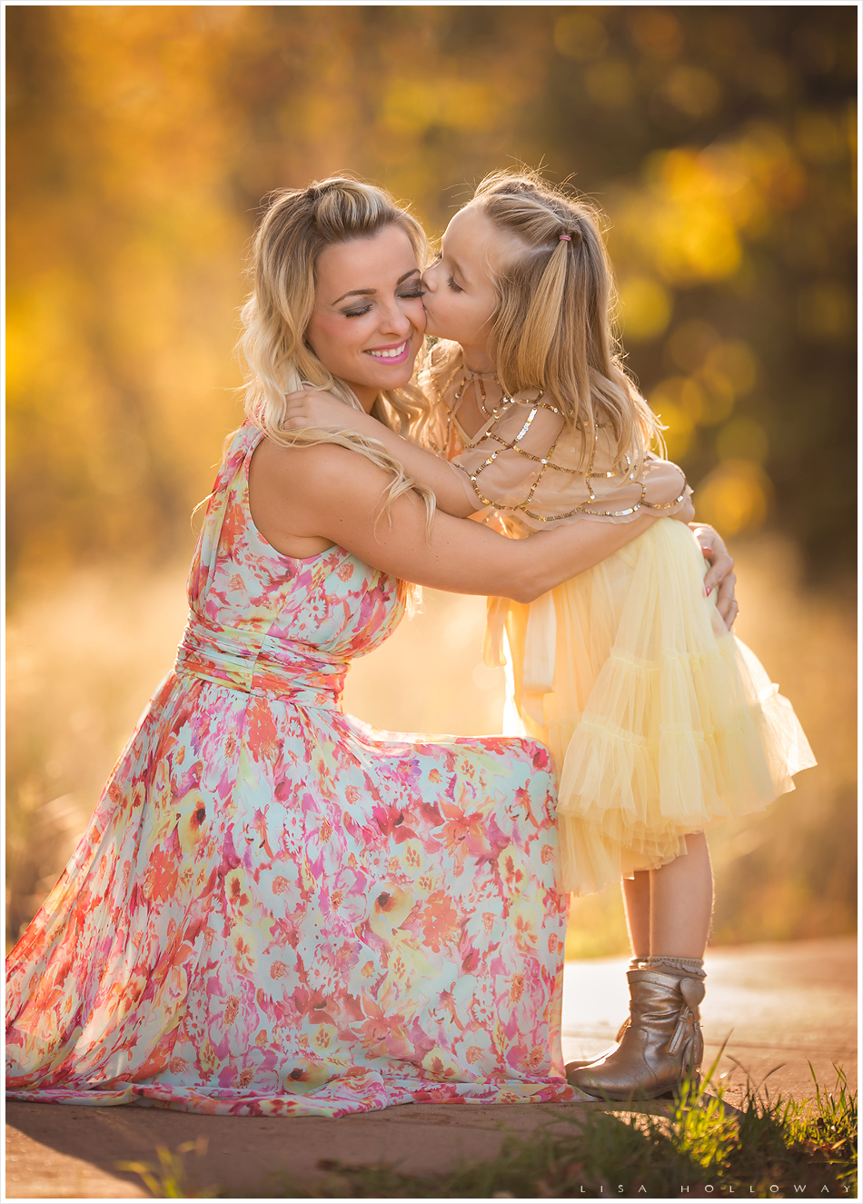 Young girl in yellow dress gives her mother a kiss on the cheek. LJHolloway Photography is a Las Vegas family photographer.
