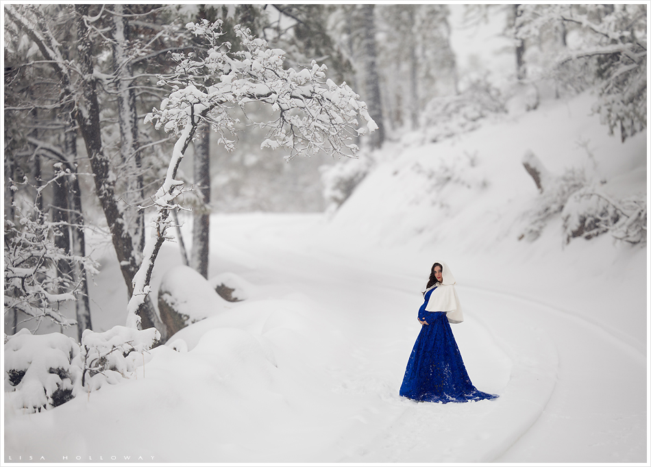Beautiful pregnant woman with a royal blue dress and white cloak stands on a snowy road