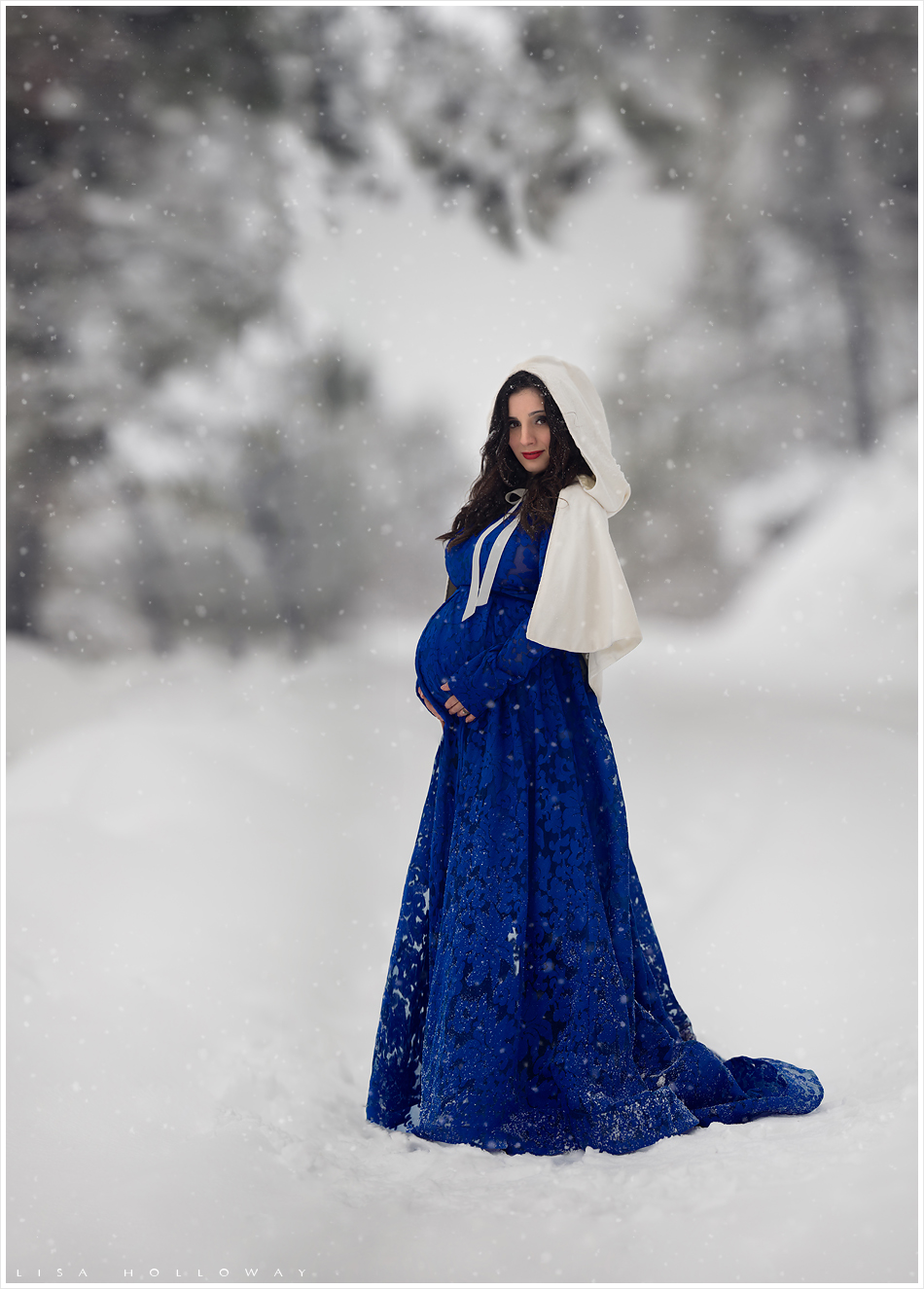 Beautiful pregnant woman with a royal blue dress and white cloak stands on a snowy road lined with snow covered trees. LJHolloway Photography is a Las Vegas Maternity Photographer.