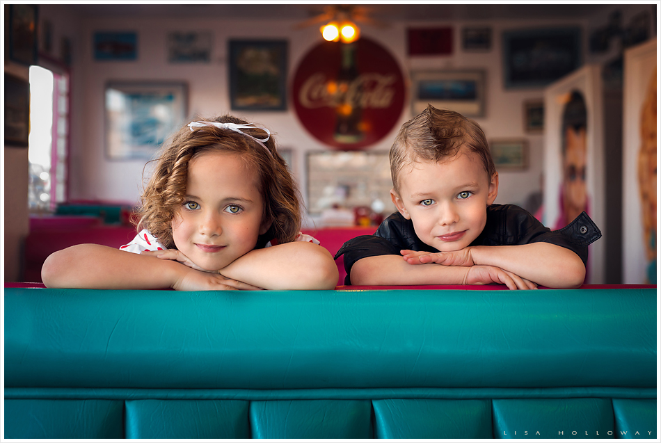 Adorable little boy and girl pose in a booth in a retro 1950s diner for a