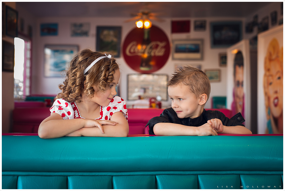 Adorable little boy and girl pose in a booth in a retro 1950's diner for a themed photo shoot. LJHolloway Photography is a Las Vegas Child Photographer.