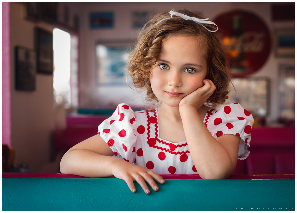 Adorable little girl in a red polka dot dress with curly hair who likes like Shirley Temple sit's in a 1950's diner. LJHolloway Photography is a Las Vegas Child Photographer.