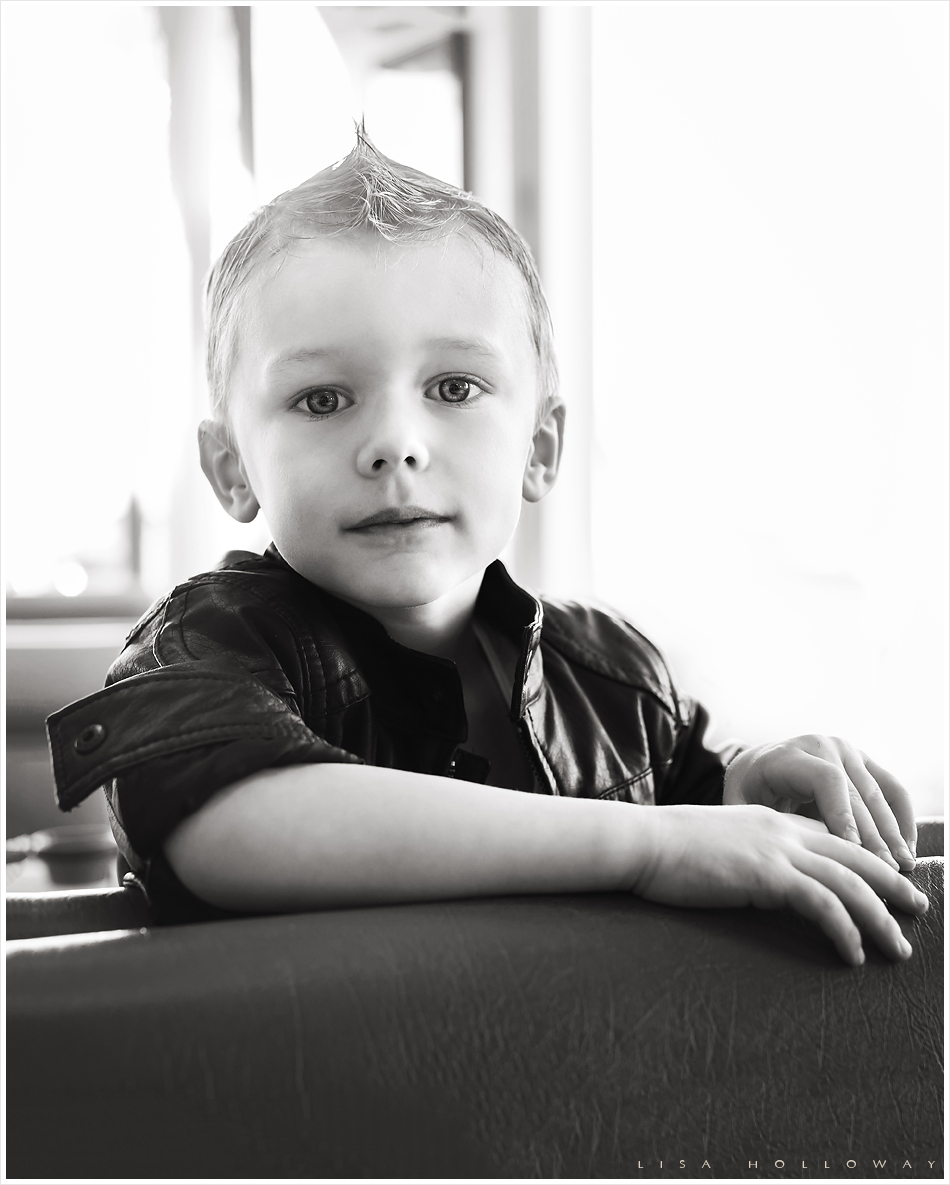 Black and white portrait of a handsome little boy in a leather jacket. LJHolloway Photography is a Las Vegas Child Photographer