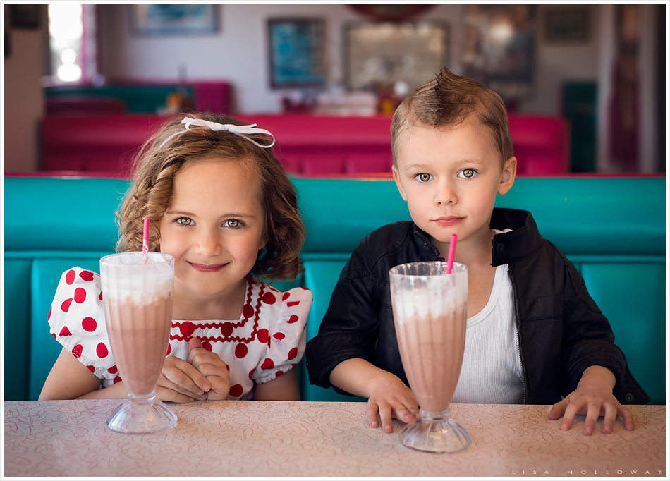Adorable little boy and girl drink milk shakes in a retro 1950's diner for a themed photo shoot. LJHolloway Photography is a Las Vegas Child Photographer.