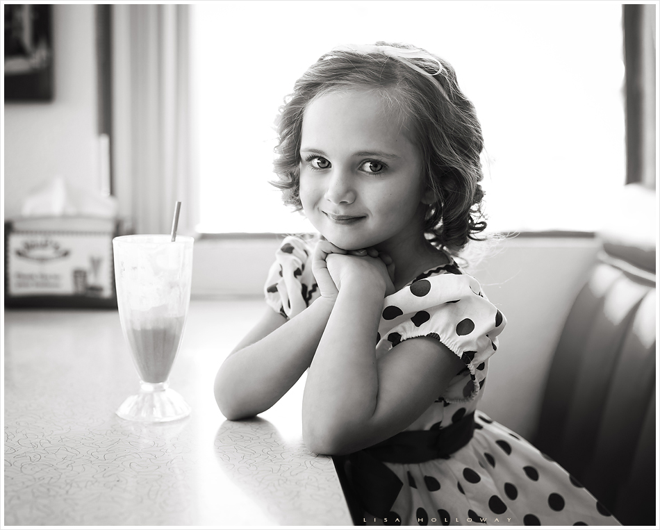 Adorable black and white portrait of a little girl in a red polka dot dress with curly hair who likes like Shirley Temple sit's in a 1950's diner. LJHolloway Photography is a Las Vegas Child Photographer.