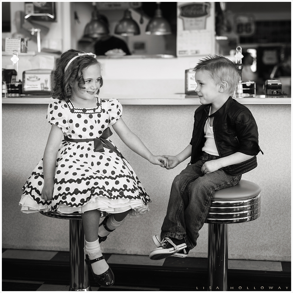 Black and white portrait of a little boy and girl in a retro 1950's diner on Route 66. LJHolloway Photography is a Las Vegas Child Photographer.