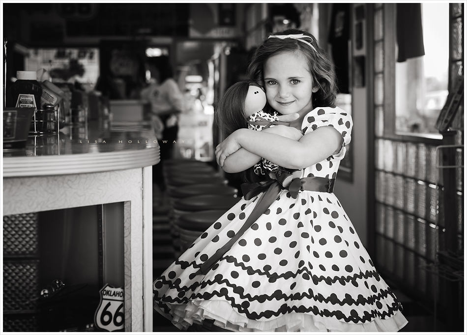 Little girl dressed as Shirley Temple plays with a matching doll in a retro 1950's Route 66 diner for a themed photo shoot. LJHolloway Photography is a Las Vegas Child Photographer.