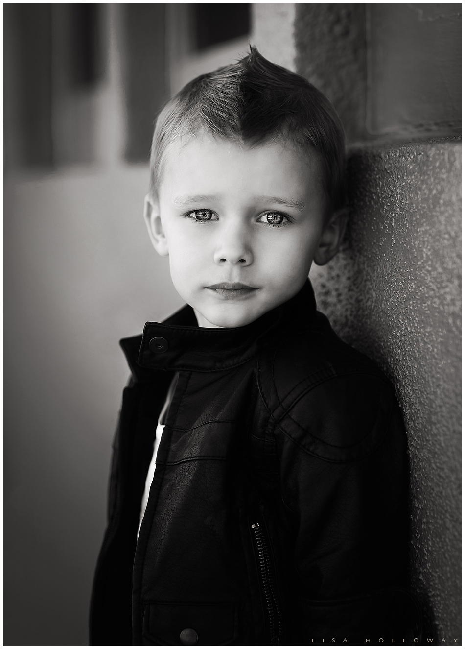 Black and white portrait of a handsome little boy in a leather jacket. LJHolloway Photography is a Las Vegas Children's Photographer
